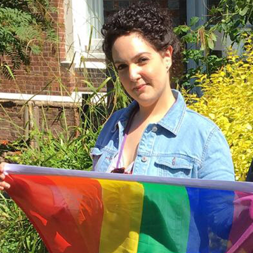 A person with short hair and a denim jacket holds a rainbow flag in front of them