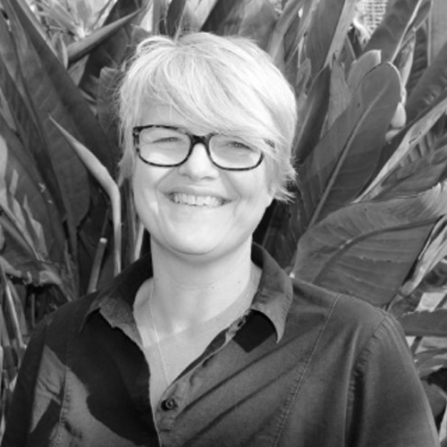 A black and white picture of a smiling person stood in front of a large tropical plant.