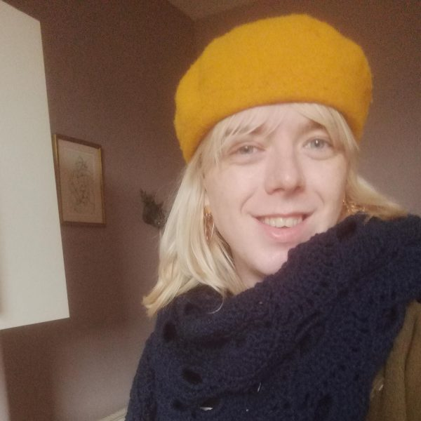 A person wearing a yellow beret and a woolly scarf smiles at the camera.